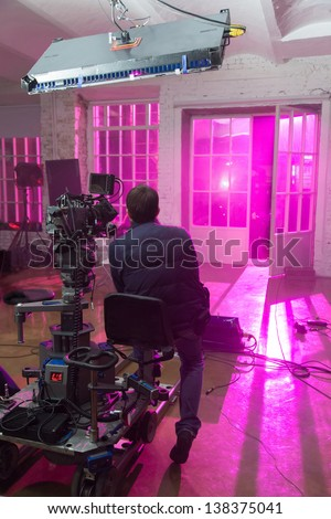 The camera shoots a scene with purple room, filmed in a rented public studio. - stock photo