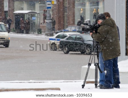 The cameraman carries on the reporting in a strong blizzard - stock photo