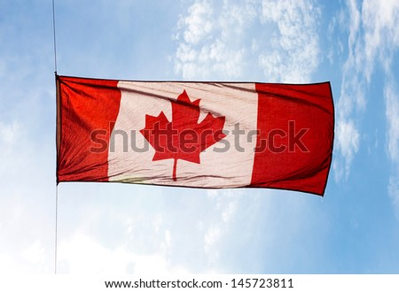 The Canadian Flag in the wind against the sky - stock photo