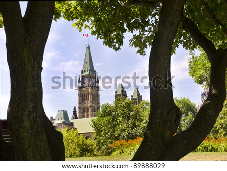 The Canadian Parliament Centre Block seen through tree trunks in Major's Hill Park in Ottawa Canada.