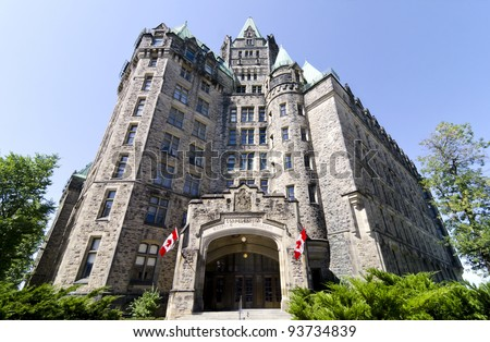 The Canadian Parliament Confederation Building with flag on Wellington Street in Ottawa during Summer.