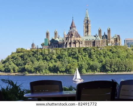 The Canadian Parliament with sailboat on the river. - stock photo