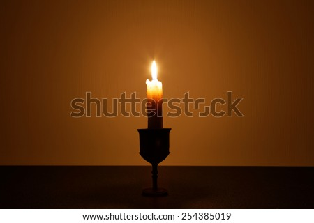 The candle's image against a wall and fades into a shadow.  - stock photo