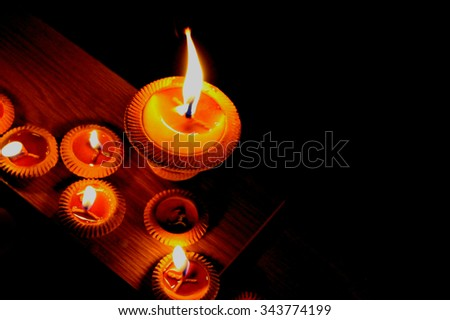 The candle with black background space on the right side for text, selective focus on the biggest candle  - stock photo