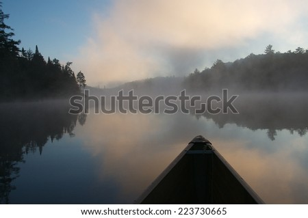 The canoe is pointing the way on a calm autumn morning over the misty lake - stock photo