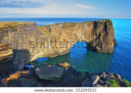 The cape Dirkholaey in the south of Iceland. The enormous rock elephant it is lit with a summer. The sunset in July - stock photo