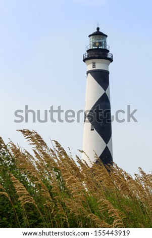 The Cape Lookout Lighthouse, with its distinctive back and white diamond pattern, stands on North Carolina's Southern Outer Banks with sea oats in the foreground.
