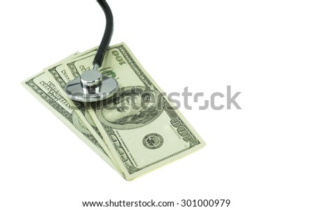 The capsule of a medical stethoscope placed on top of hundred dollar bills, conceptual image about the cost of medical expenses or financial health - stock photo