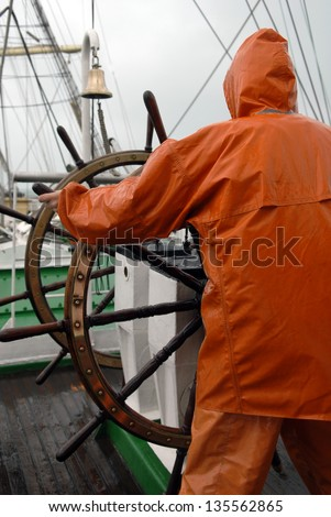 The captain at the helm of the ship - stock photo