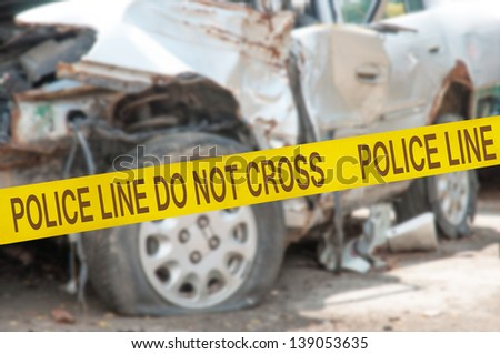The car accident behind Police Line Do Not Cross barrier tape - stock photo