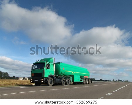 The car for transportation of fuel to the background of the rural landscape.Motor Tanker with the tank