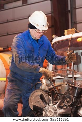 The car mechanic repairs the car engine - stock photo