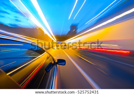 The car moves at fast speed at the night. Blured road with lights with car on high speed.