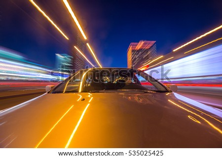 The car moves at great speed at the night. Blured road with lights with car on high speed. The view from the front to back.