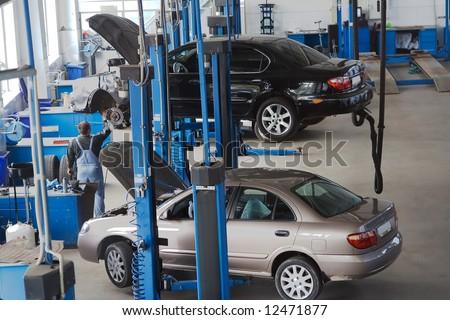 the car service sedan under repairmen t work of mechanizer on elevator - stock photo