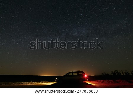 The car with the headlights switched on the background of the Milky Way in the starry sky. - stock photo