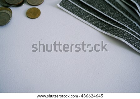 The carbon payslips on white background with the coins out of focus,Focusing on white background,The Salary payroll slip.Soft focus. - stock photo