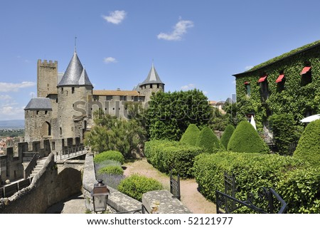 The Carcassone castle in Southern France by day against a blue sky with clouds.