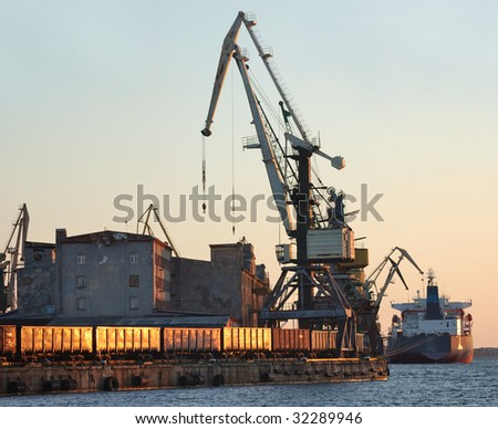 The cargo ship is loaded by coal in Riga port. - stock photo
