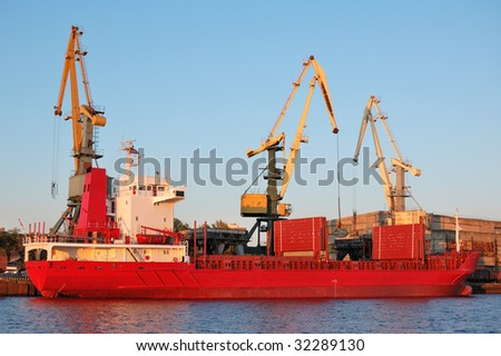 The cargo vessel is loaded by coal in Riga port. - stock photo