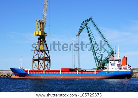 The cargoship and the crane on a background of the blue sky