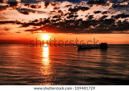 The cargoship floats against a beautiful sunset - stock photo