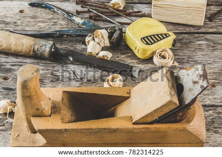 The carpenter tools on wooden bench, plane, chisel,mallet, tape, hammer, tongs, nails and saw the view from the top