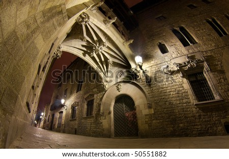 "The Carrer del Bisbe street is one of the most popular venues of the gothic quarter (""barri gotic"") of Barcelona. In this area, streets are narrow and old - at night, they look mysterious and magical. - stock photo"