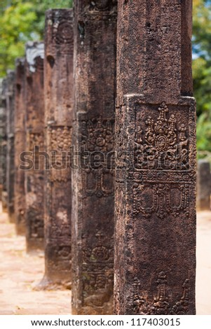 The carved columns of the audience hall lined up in a row at Polonnaruwa, the ancient capitol of the kingdom of Sri Lanka - stock photo