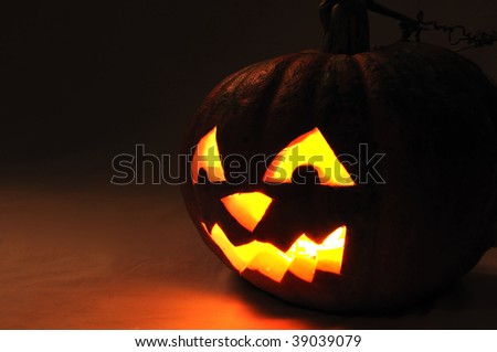 The carved face of pumpkin glowing on Halloween - stock photo