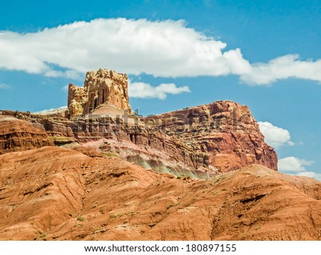 The Castle, a rock formation at Capitol Reef National Park, stands tall against a cloudy blue Utah sky. - stock photo