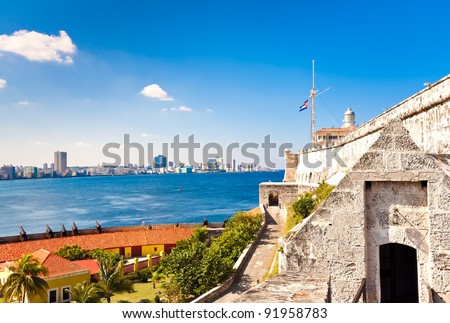The castle and lighthouse of El Morro in Havana with a view of the city in the background - stock photo