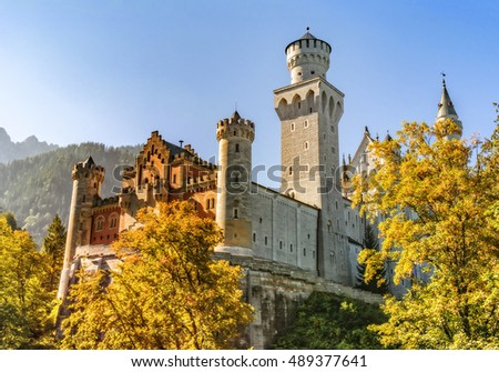 "The castle ""Neuschwanstein"" in Germany surrounded by trees with autumn colors"
