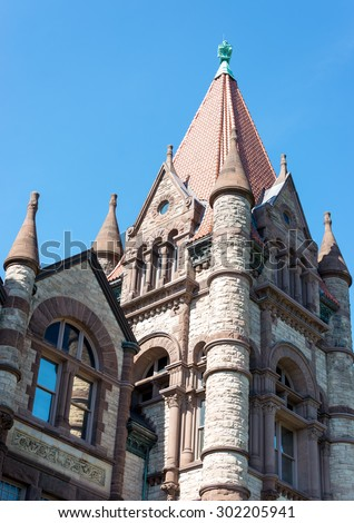 The castle shaped historic building of Victoria College at university of Toronto. The building has cylindrical pillars on corners with cone structure on the top. - stock photo