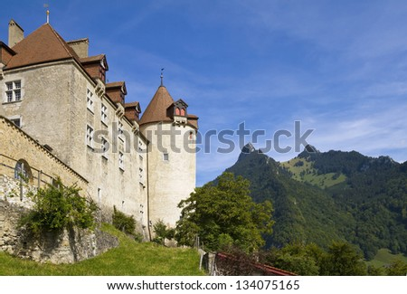 The castle towers above the medieval town of Gruyeres. - stock photo