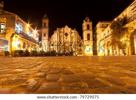 The Cathedral of Havana and its adjacent square and restaurant in the colonial neighborhood of Old Havana illuminated at night - stock photo