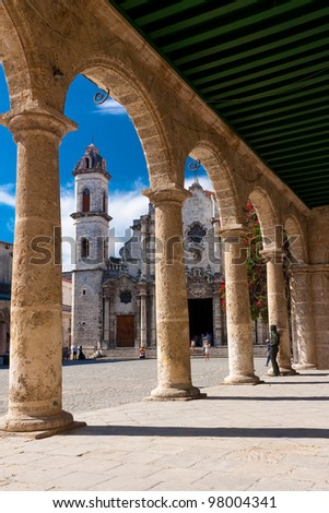 The Cathedral of Havana and its adjacent square seen through the porticoes of a nearby spanish colonial palace - stock photo