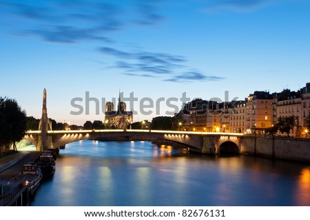 """The cathedral of Notre-Dame in the background and the bridge """"Pont de la Tournelle"""" in the foreground - stock photo"""