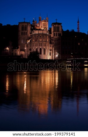 The cathedral Saint-Jean-Baptiste shot at dusk with irs reflection in the river La Saone. On top is also visible the Notre-Dame de Fourviere basilica - stock photo