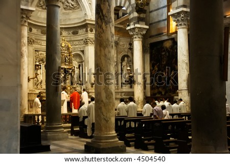 The Catholic priests inside the cathedral in Pisa on the field of miracles. - stock photo