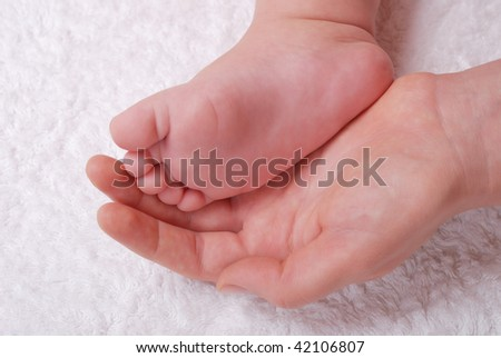 The caucasian baby feet in mommy's hands - stock photo