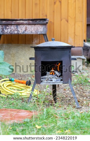 the cauldron on open fire in the yard - stock photo