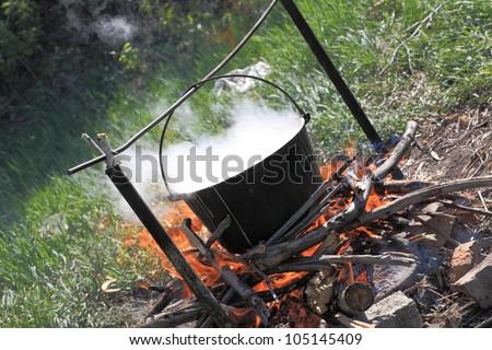 The cauldron with steam on a bonfire - stock photo