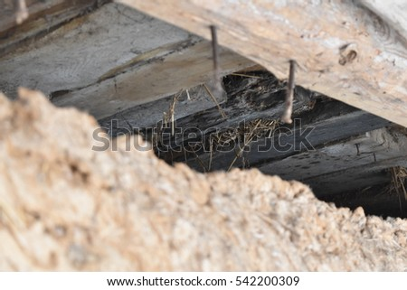 the ceiling of the old house with a hole and nails