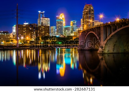 The Central Avenue Bridge and skyline reflecting in the Mississippi River at night, in Minneapolis, Minnesota. - stock photo
