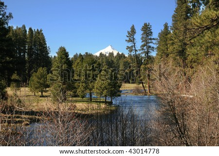 the central Oregon Cascade volcano Mount Jefferson behind the head of the Metolius River - stock photo