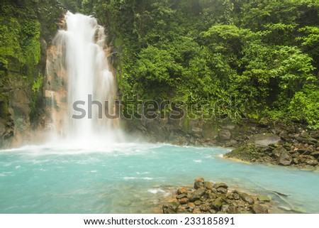 The cerulean blue waters of the Rio Celeste Waterfall in Volcan Tenorio National Park, Costa Rica. - stock photo