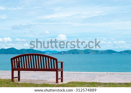 The chair sits alone by the sea. - stock photo