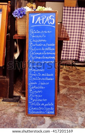 the chalkboard menu in a restaurant in Spain, with different spanish tapas, such as patatas bravas or tortilla de patatas - stock photo