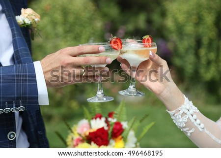 the champagne glasses in the hands of the newlyweds. close-up , outdoors.